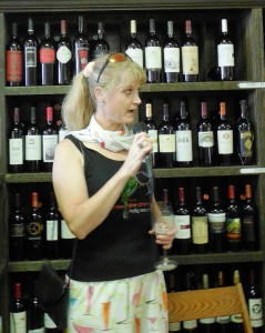 Michelle Brady emceeing in front of shelves of wine