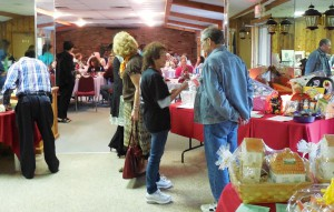 Overview of attendees dining and viewing silent auction item